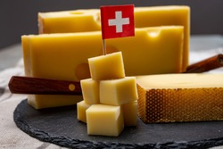Swiss cheeses, block of medium-hard yellow cheese emmental or emmentaler with round holes and matured gruyere close up served in cubes as mountain top with Swiss flag.