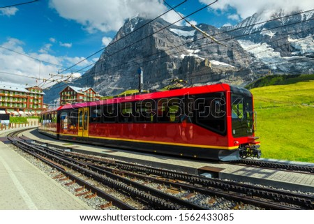 Swiss excursion destination. Travel and touristic place with stunning view. Modern electric red tourist train in Kleine Scheidegg station, Grindelwald, Bernese Oberland, Switzerland, Europe #1562433085