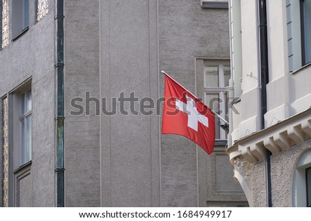 Swiss Flag hanging from Building Facade. Stockfoto ©