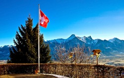 Swiss flag over mountains