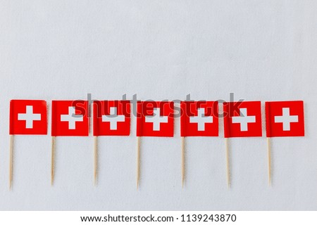 Swiss flags on wooden toothpicks used to decorate the traditional swiss bread baked on Swiss National Day on August 1st. White background, isolated, copy space.