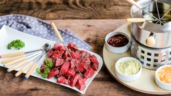 swiss specialty, the fondue bourguignonne with pice of meat and many sauces on wooden table