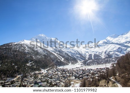 Swiss village surrounded by a snow-covered mountain range in Saas Fee #1101979982