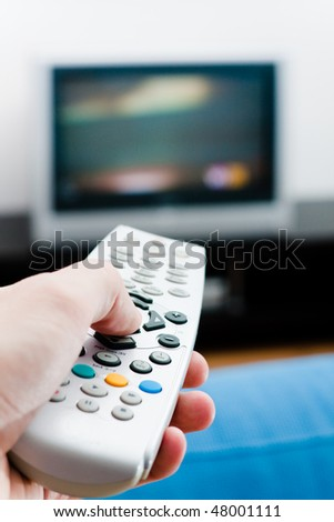 Switching the channels. Hand with remote TV control