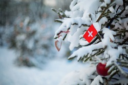 Switzerland flag. Christmas holiday greeting card. Christmas tree covered with snow and a Swiss flag. Winter scene background outdoor. Xmas card