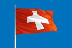 Switzerland national flag waving in the wind on a deep blue sky. High quality fabric. International relations concept.