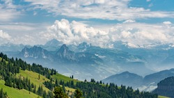 Switzerland, Panoramic view on green Alps and Mythens in clouds