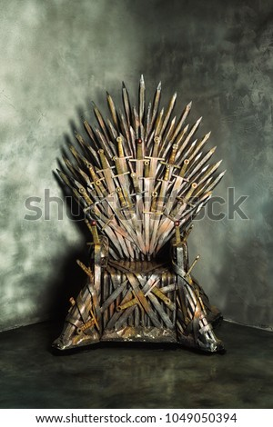 Swords vintage throne at a grunge dark wall indoors background. #1049050394