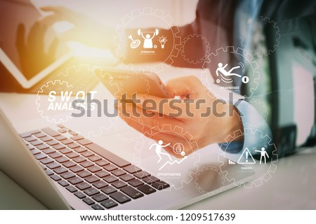 SWOT Analysis virtual diagram with Strengths, weaknesses, threats and opportunities of company.Hands of businessman using mobile phone in modern office with laptop and digital tablet computer
