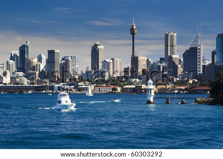 sydney australia CBD close-up with lighthouse and boat in harbour water blue sky skyscrapers
