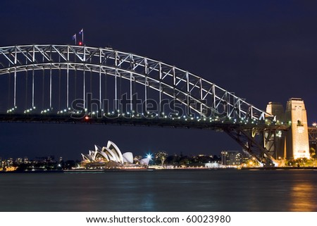 sydney australia harbour bridge opera house night scene highlighted illuminatoin by lights blue sky