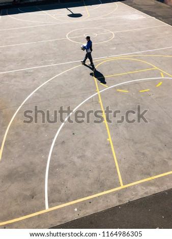 Sydney, Australia - July 20, 2018: A man holding a box walking across a basketball court. #1164986305