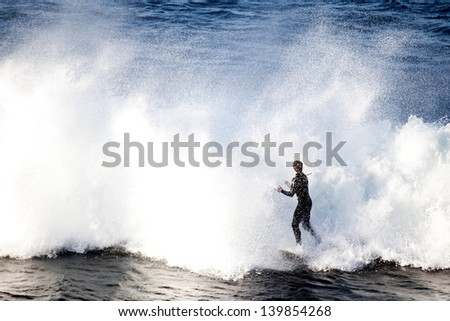 SYDNEY, AUSTRALIA - JULY 1: An unidentified surfer tackles sudden high waves of the Tasman Sea near Shelly Beach in Sydney, Australia on July 1, 2012