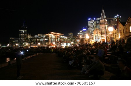 SYDNEY, AUSTRALIA - JUNE  12, 2009: Tourists watch the light displays at Campbells Cove held as part of the Vivid Sydney Festival, June 12, 2009