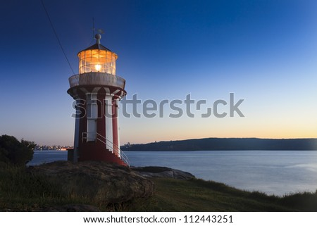 Sydney Australia lighthouse at South Head illuminated light at sunrise navigating entrance to harbour for ships - stock photo