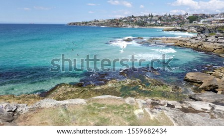 Sydney, Australia- November 4, 2019: Tamarama Point, Coastal view showing distant surfers and lovely rocky beachside view with clear blue waters on a sunny day. #1559682434