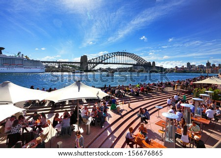 SYDNEY AUSTRALIA - SEPTEMBER 15, 2013: Residents and visitors dine, relax and basque in the glorious afternoon sun quayside by the harbour, Sydney Australia.