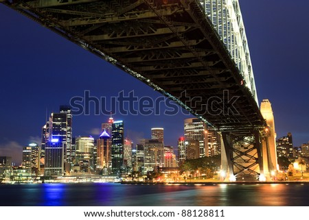 Sydney Australia view on CBD from under harbour bridge giant still arch close-up at dusk time with illuminated skyscrapers