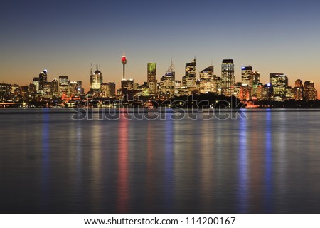 Sydney cbd cityscape at sunset with illuminated lights reflected in sydney harbour waters