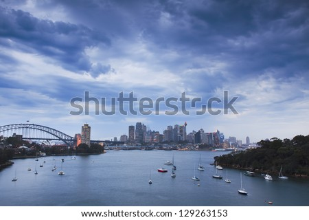 sydney city cbd and harbour bridge at thunderstorm weather with heavy clouds over harbour water with boats at sunset