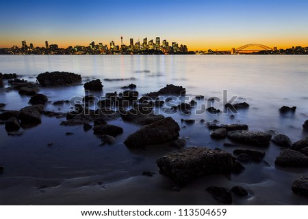 sydney city CBD and harbour bridge sunset view at low tide with sea floor foreground and lights reflection