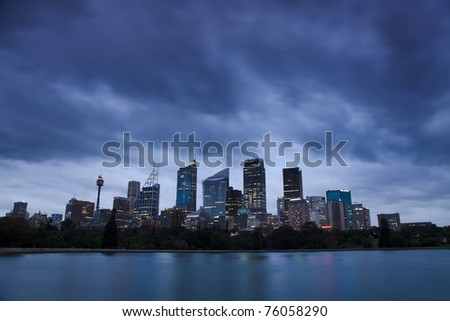 sydney city CBD skyscrapers view over harbour twilight time with heavy cloudy overcast illuminated windows of cityscape