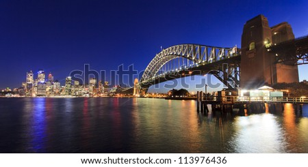 Sydney city CBD view across harbour along Bridge illuminated at sunset lights reflected in water australia landmarks