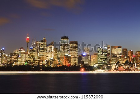 Sydney city cbd view at sunset over harbour with reflection of light illuminated skyscrapers towers and landmark buildings