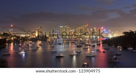 sydney city CBD view from Waverton at sunset with illuminated downtown lights reflect in harbour water crowded with heaps of yachts and boats