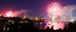 Sydney City fireworks new year celebration light show dusk lights reflection in harbour over CBD and bridge