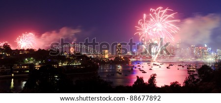 Sydney City fireworks new year celebration light show dusk lights reflection in harbour over CBD and bridge - stock photo