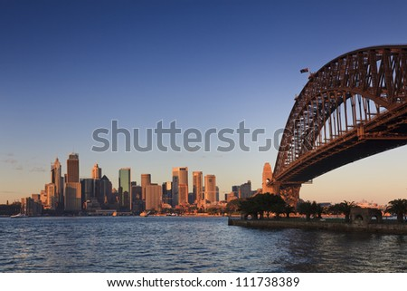 Sydney city harbour and bridge cityscape panoramic view at sunrise with warm sun light blue and pink sky
