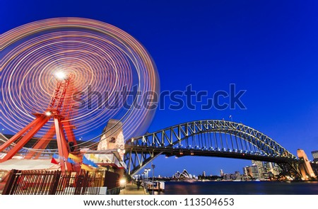 sydney city luna park wheel with harbour bridge arch at sunset illuminated lights and blurred motion
