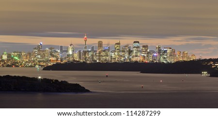 sydney city panorama view from north head at sunset with brown light, cbd illumination, still water and clouds at harbour