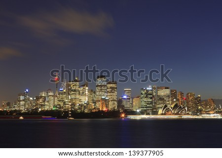 Sydney cityscape at sunset illuminated skyscrapers australia landmark over harbour water