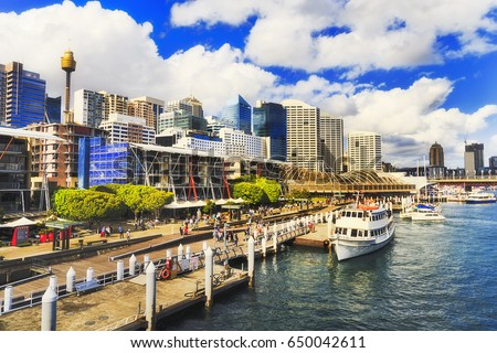Photo of  Sydney Darling Harbour Kings wharf with docked ship along the pier with modern architecture towers and skyscrapers on a sunny summer day.