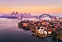 Sydney harbour and major city landmarks of waterfront around Sydney Harbour bridge in aerial view at pink sunrise.