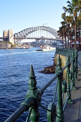 Sydney Harbour Bridge from Circular Quay with railings detail and North Sydney in the background.