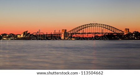 Sydney Harbour Bridge side view at sunset orange sky behind metal arch connecting harbour sides with blurred water and lights reflection