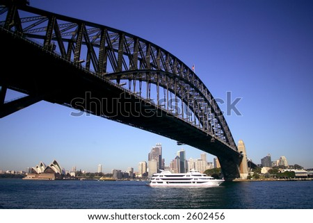 Sydney Opera House and Harbor Bridge at sunset with ferry boat