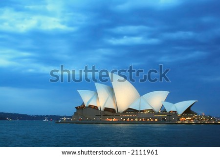 Sydney Opera House at dusk with cloudy skies overhead