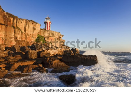 Sydney South Head nautical lighthouse at sunrise sea edge landmark for sea safety on sandstone rocks and surf of waves