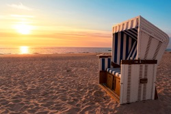 Sylt island beach scenery with empty hooded chair and fine sand on North Sea shore, at sunset. European travel destination. German beach resort.