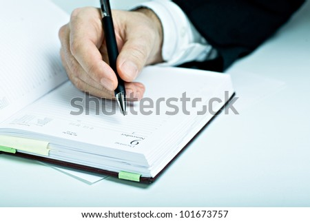 Symbilic picture. Suited man with schedule book.