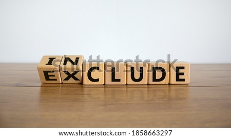 Symbol for a better inclusion. Inverted cube and changed word exclude to include. Beautiful wooden table, white background. Copy space. ストックフォト ©