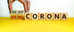 Symbol for a post-corona time. Male hand turns cubes and changes the words 'during corona' to 'post-corona'. Beautiful yellow table, white background. Medical and covid-19 post-pandemic concept.