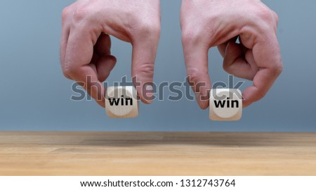 "Symbol for a win win situation. Hands are holding two dice with the words ""win"" and ""win"" in front of a grey background."