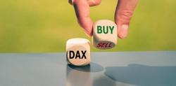 Symbol for buying stocks. Hand turns a cube and changes the word