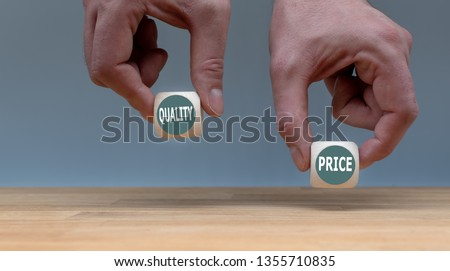 Symbol for choosing quality instead of a cheap price. Two Hands hold two dice with the words 'quality' and 'price'. The dice with the label 'quality' is chosen. Foto stock ©