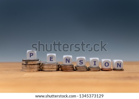 "Symbol for decreasing pensions. Dice placed on stacks of coins form the word ""PENSION"".  #1345373129"